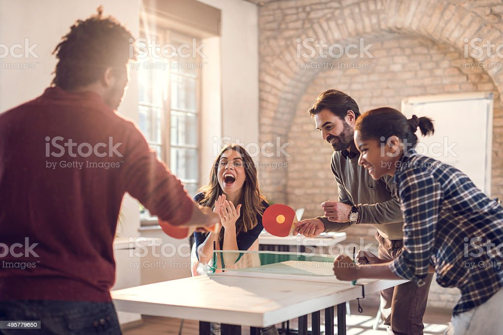 Playful business team playing table tennis at casual office. stock photo