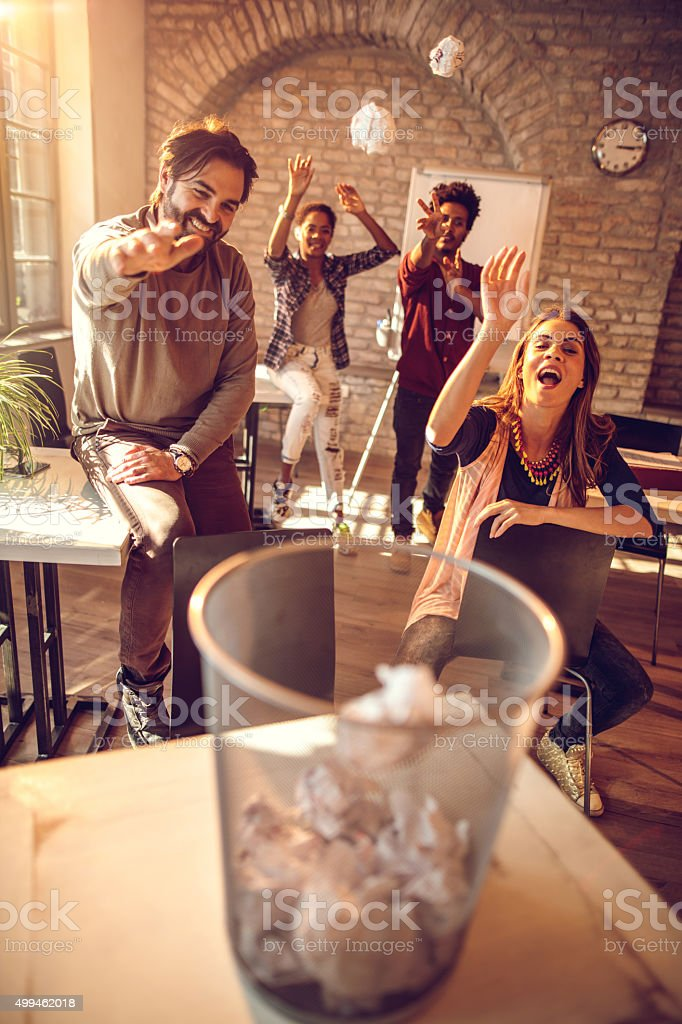 Playful business team tossing crumpled papers into the wastepaper basket. stock photo