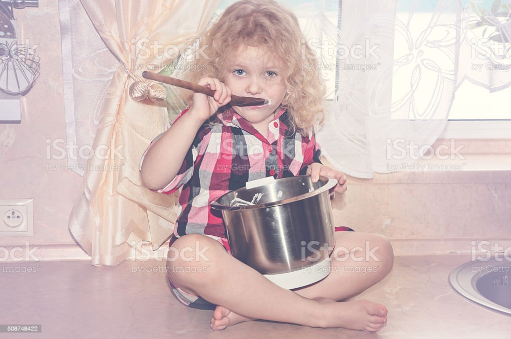 Playful child girl with kitchenware and foodstuffs in kitchen stock photo