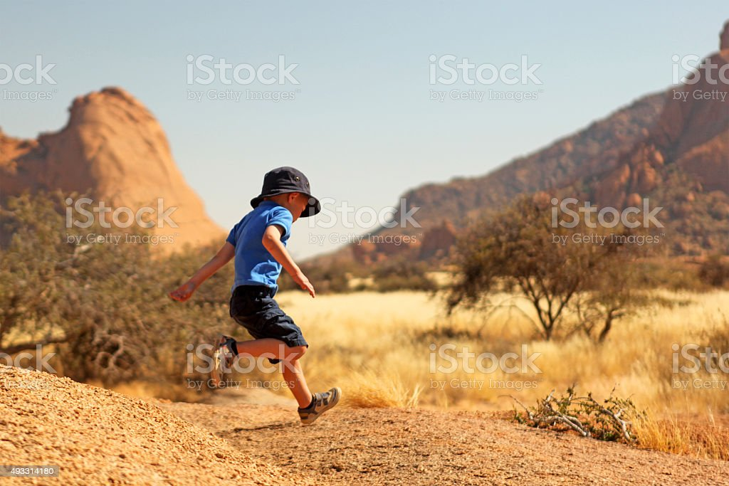 Playful Child Jumping on Rocks During Vacation in Namibia Africa stock photo