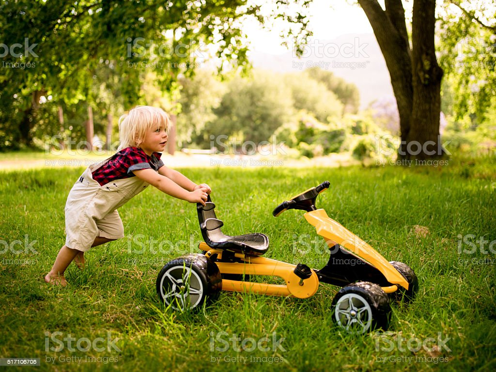 Playful child pushing his toy car at the park stock photo