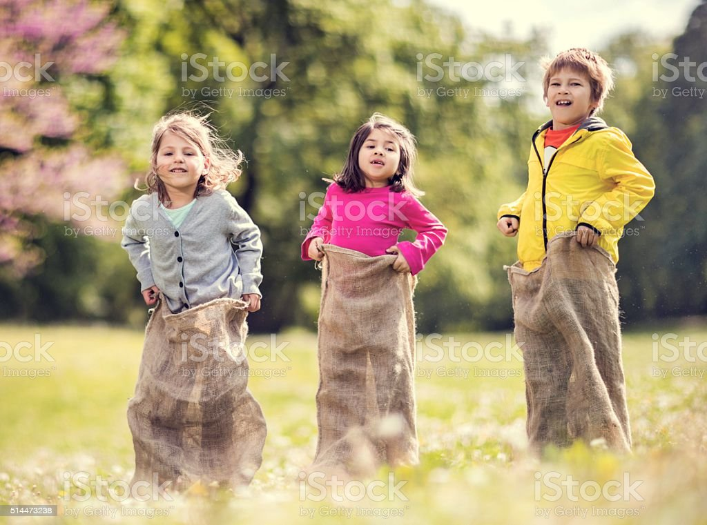 Playful children having sack race in nature. stock photo