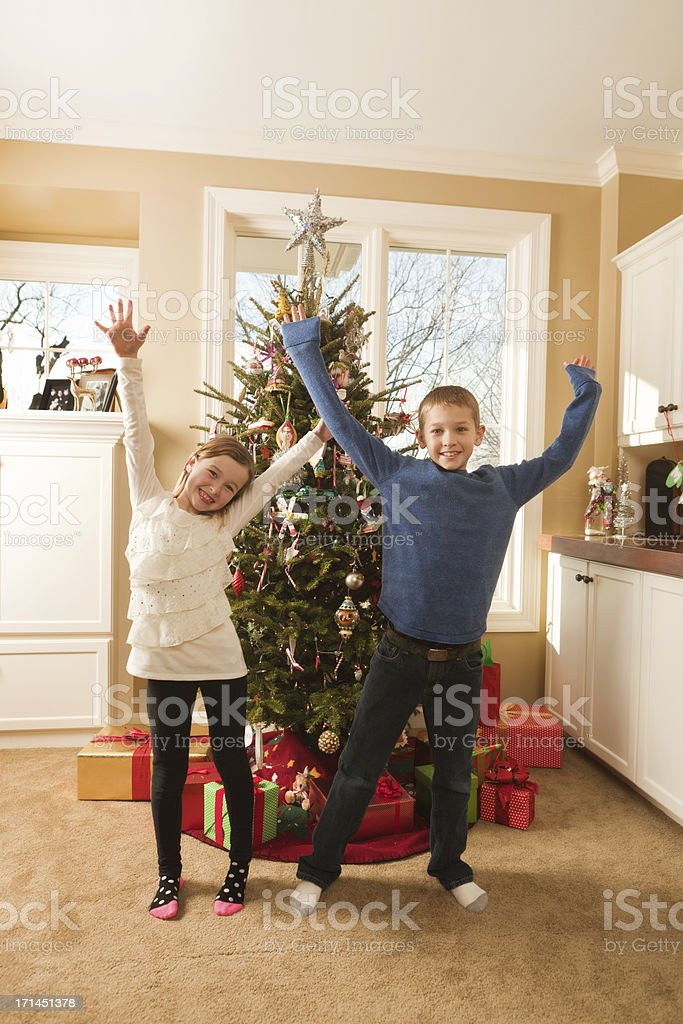 Playful Children in Front of Family Christmas Tree stock photo