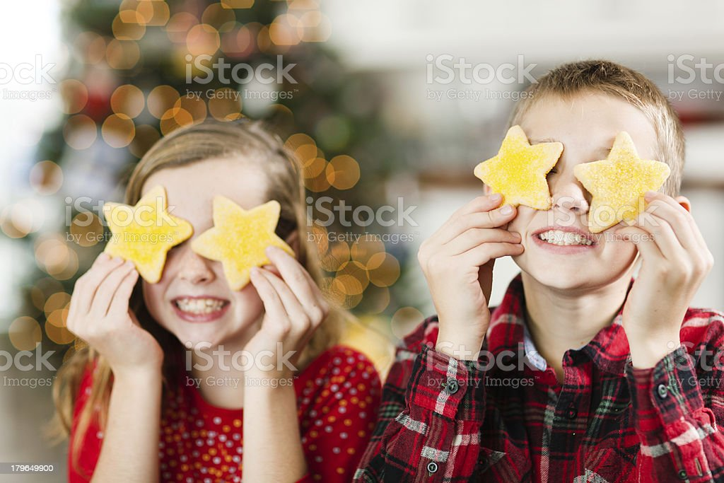 Playful Children with Christmas Cookies in front of Tree Hz royalty-free stock photo