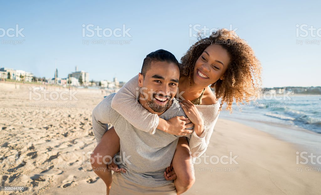 Playful couple at the beach stock photo