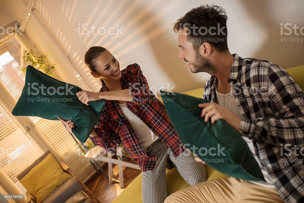 Playful couple having fun during a pillow fight at home. stock photo