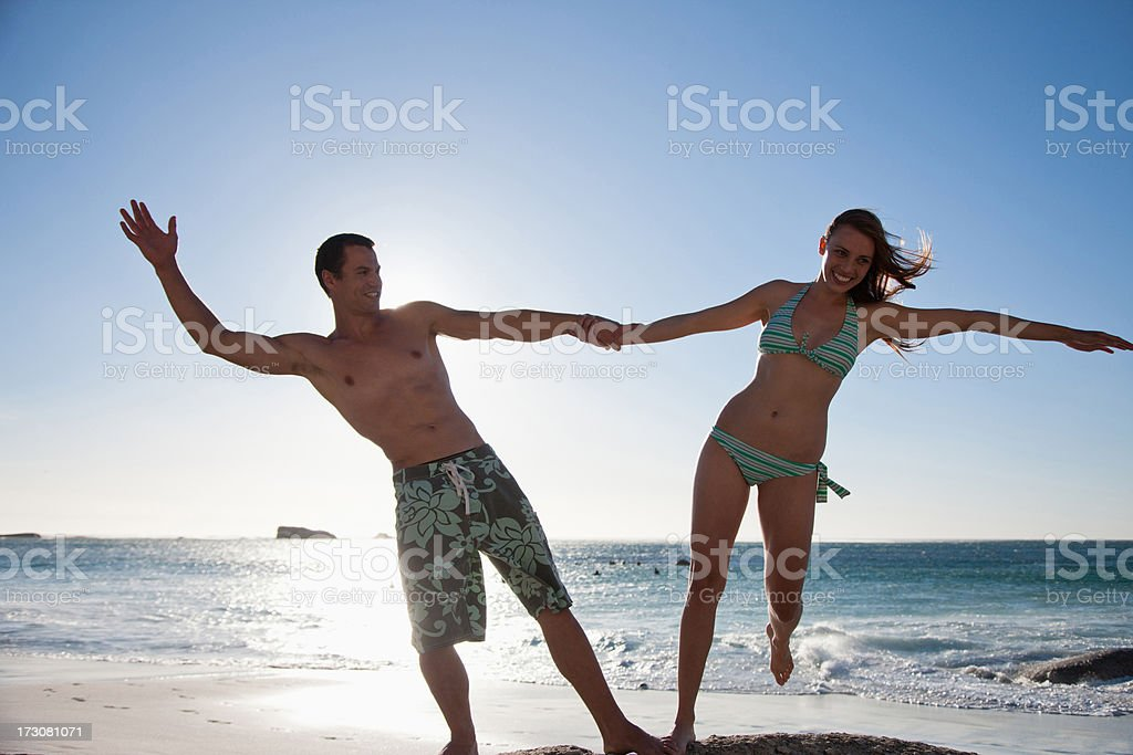 Playful couple holding hands at beach royalty-free stock photo