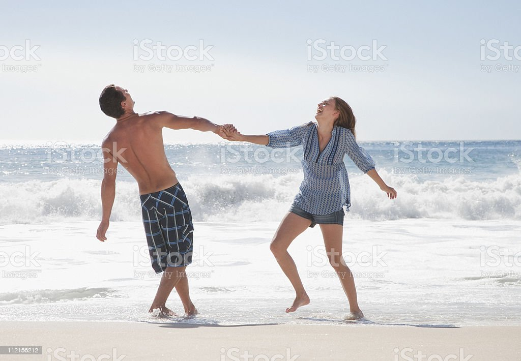Playful couple holding hands on beach royalty-free stock photo