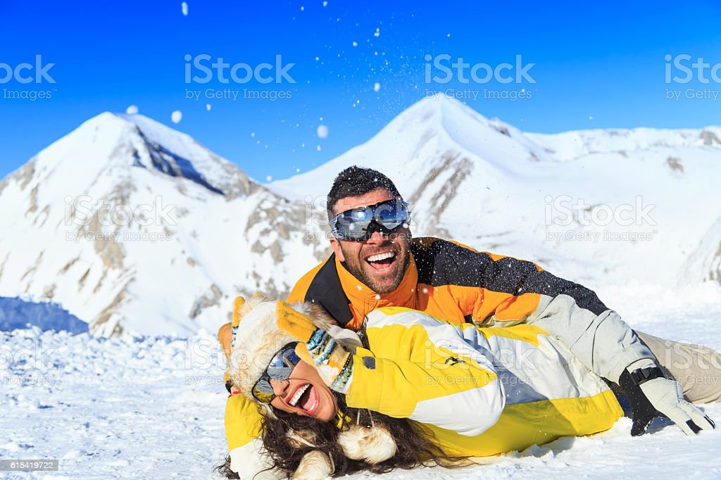 Playful couple lying on front on snow in mountain stock photo