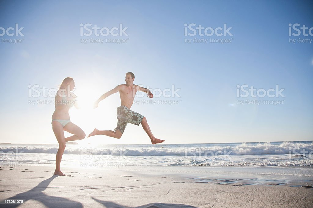 Playful couple running on beach royalty-free stock photo