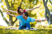Playful couple with arms outstretched having fun in the park.