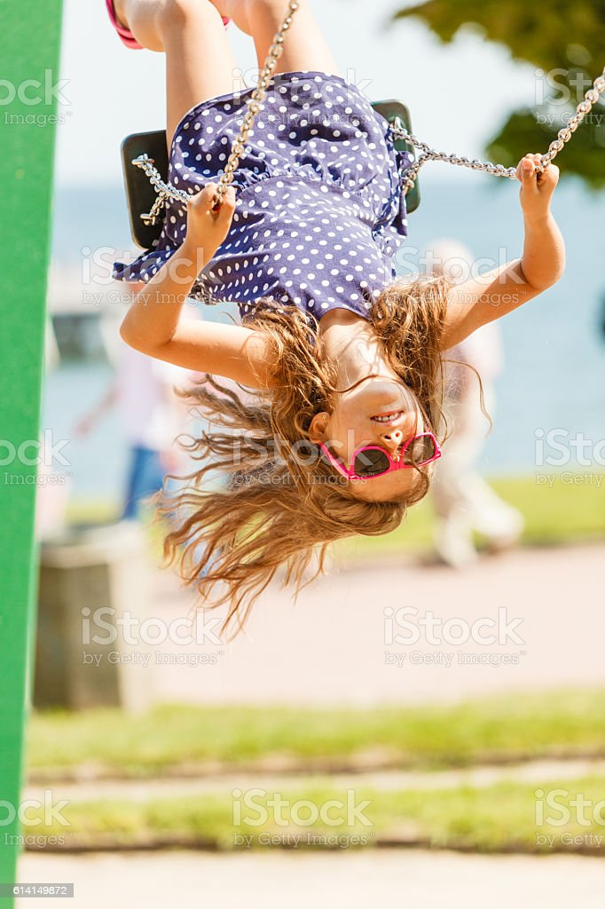 Playful crazy girl on swing. stock photo
