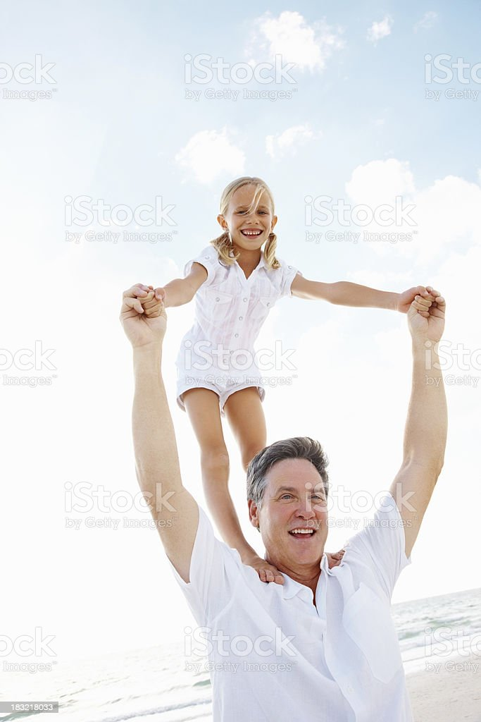 Playful daughter standing on father's shoulder at the beach royalty-free stock photo