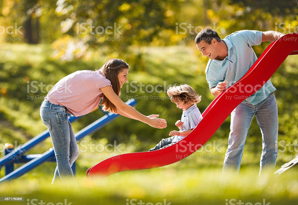 Playful family enjoying in the playground. stock photo