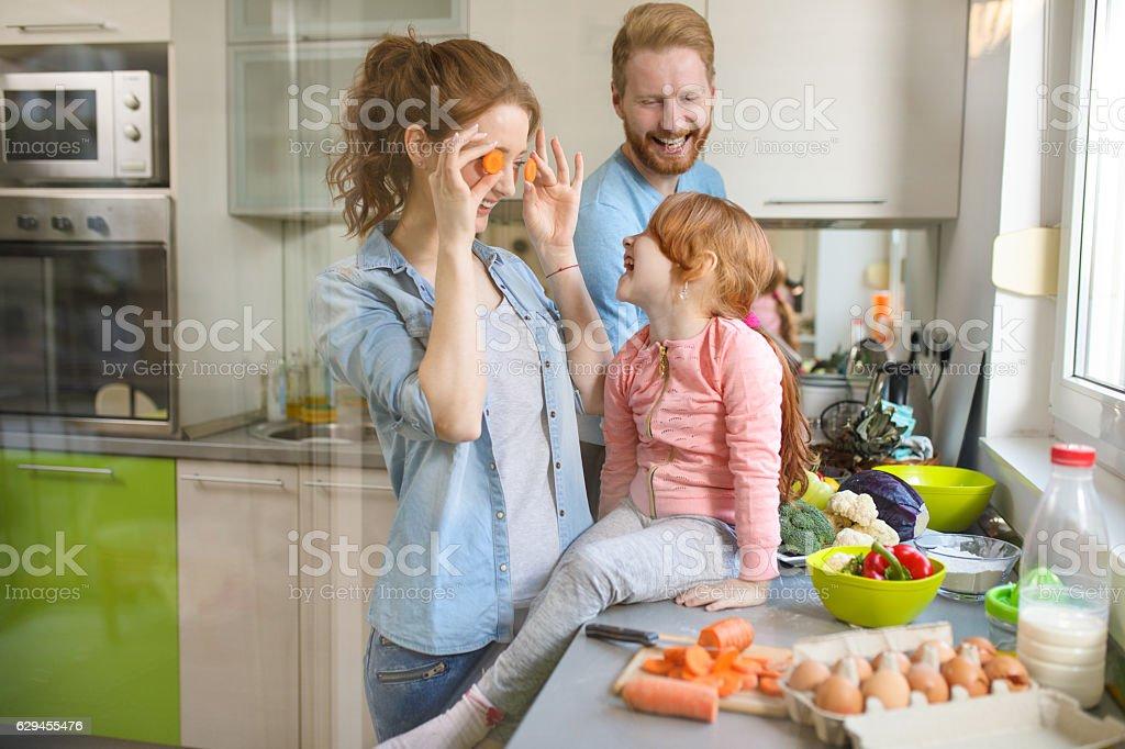 Playful family having fun preparing food in the kitchen stock photo