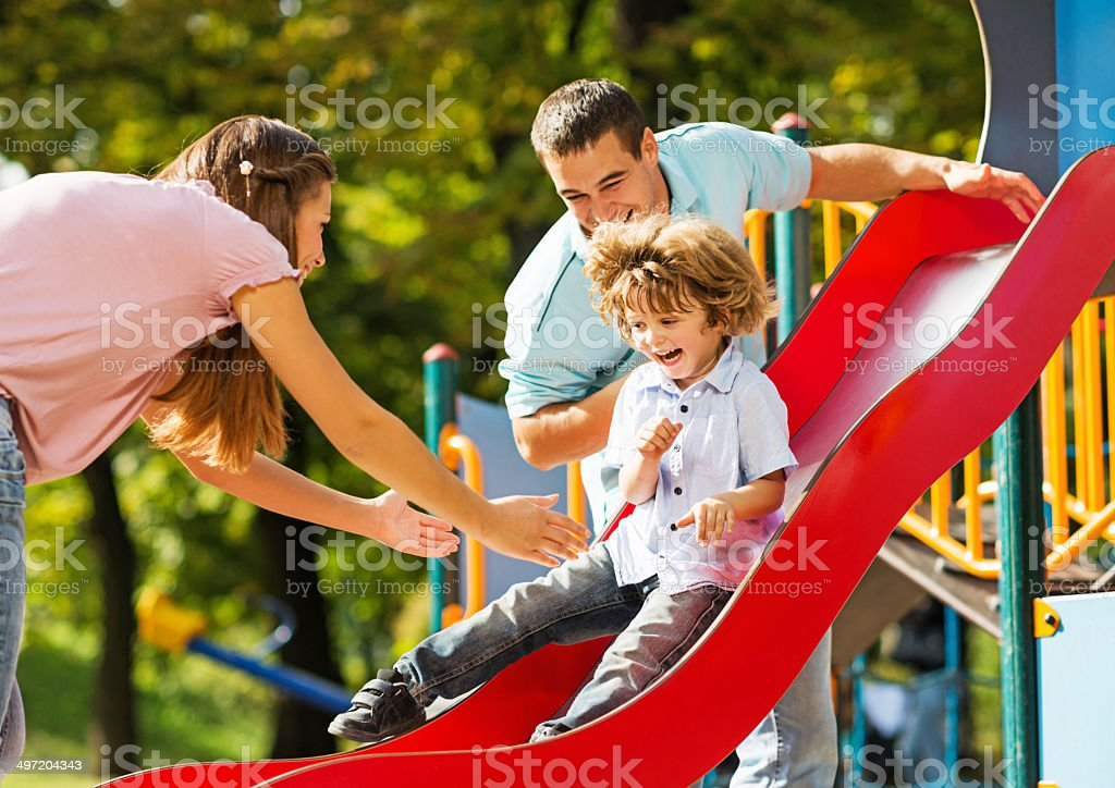 Playful family in the playground. stock photo