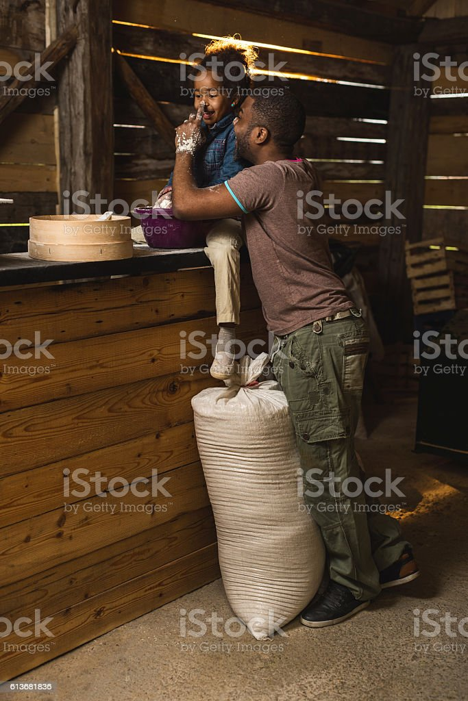 Playful father and daughter having fun with flour in mill. stock photo