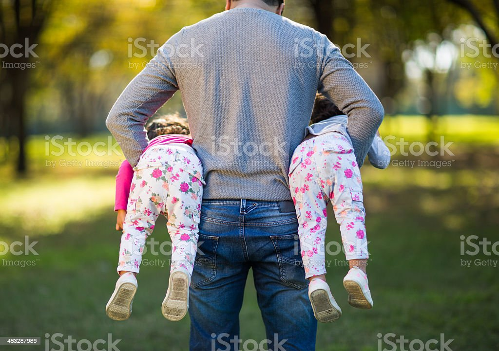 Playful father and daughters stock photo