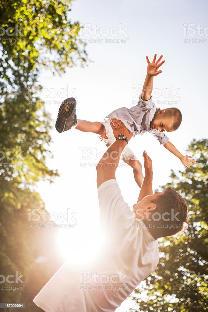 Playful father and son having fun in the park. stock photo