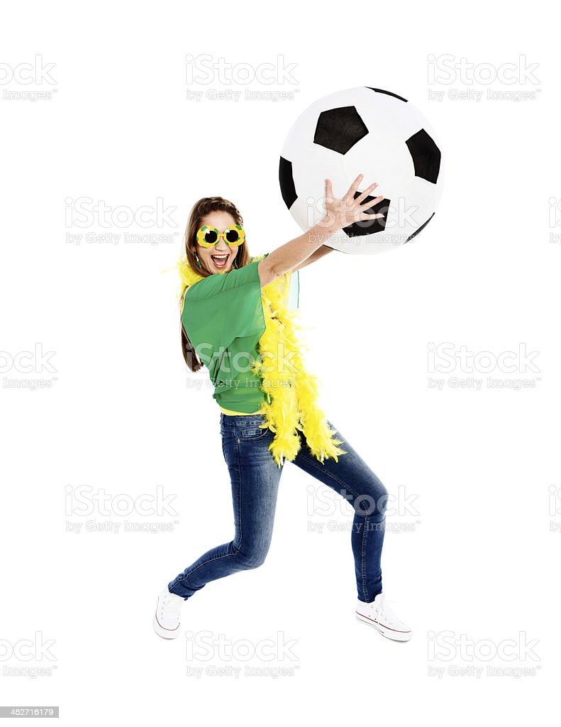 Playful female Brazilian soccer fan with giant football stock photo