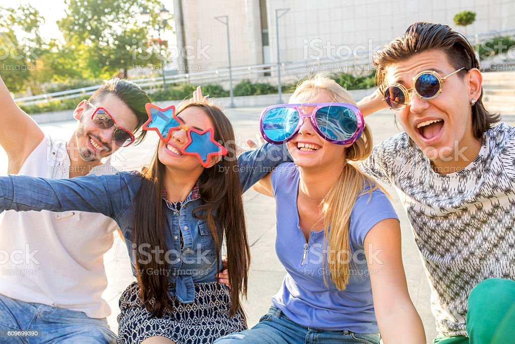 Playful friend with funny sunglasses in the city. stock photo