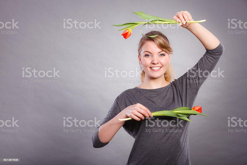 Playful girl having fun with flowers tulips. stock photo