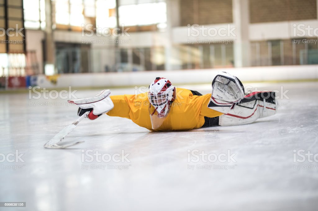 Playful ice hockey player sliding on his stomach at rink. stock photo