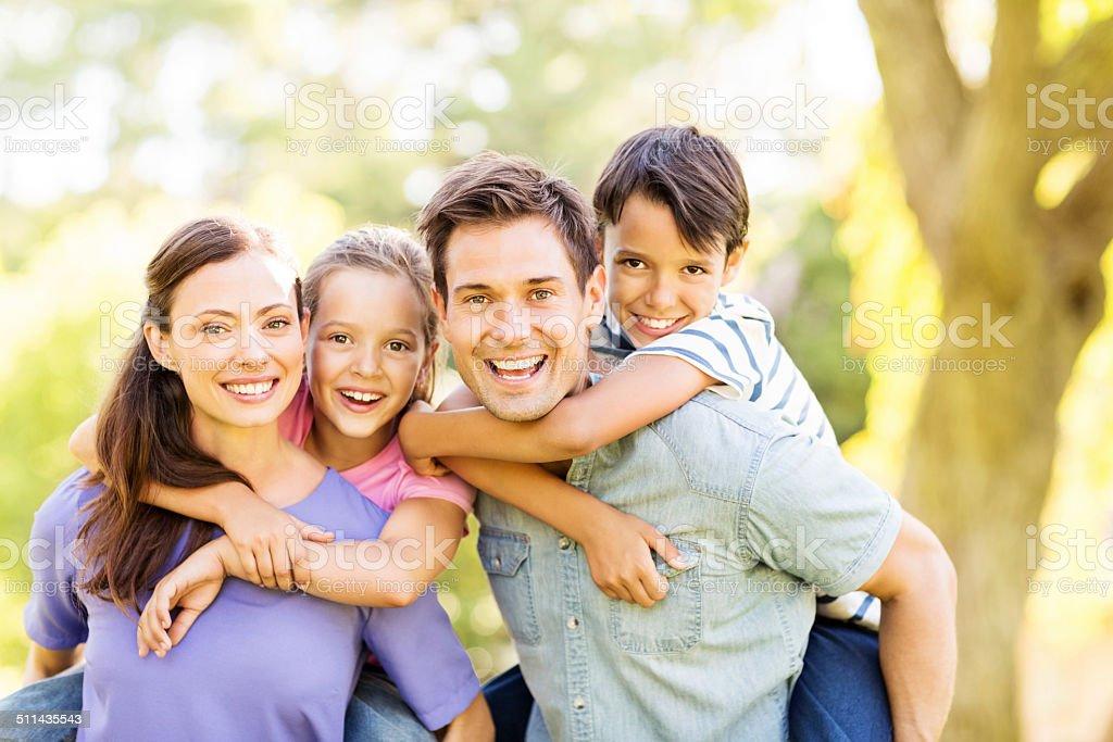 Playful Kids Enjoying Piggyback Ride On Parents stock photo