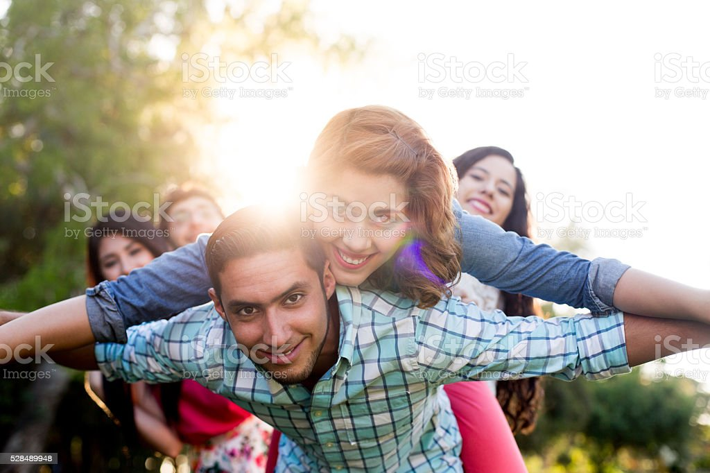 Playful latin couple with friends in background stock photo