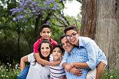 Playful latin family embracing and smiling at camera