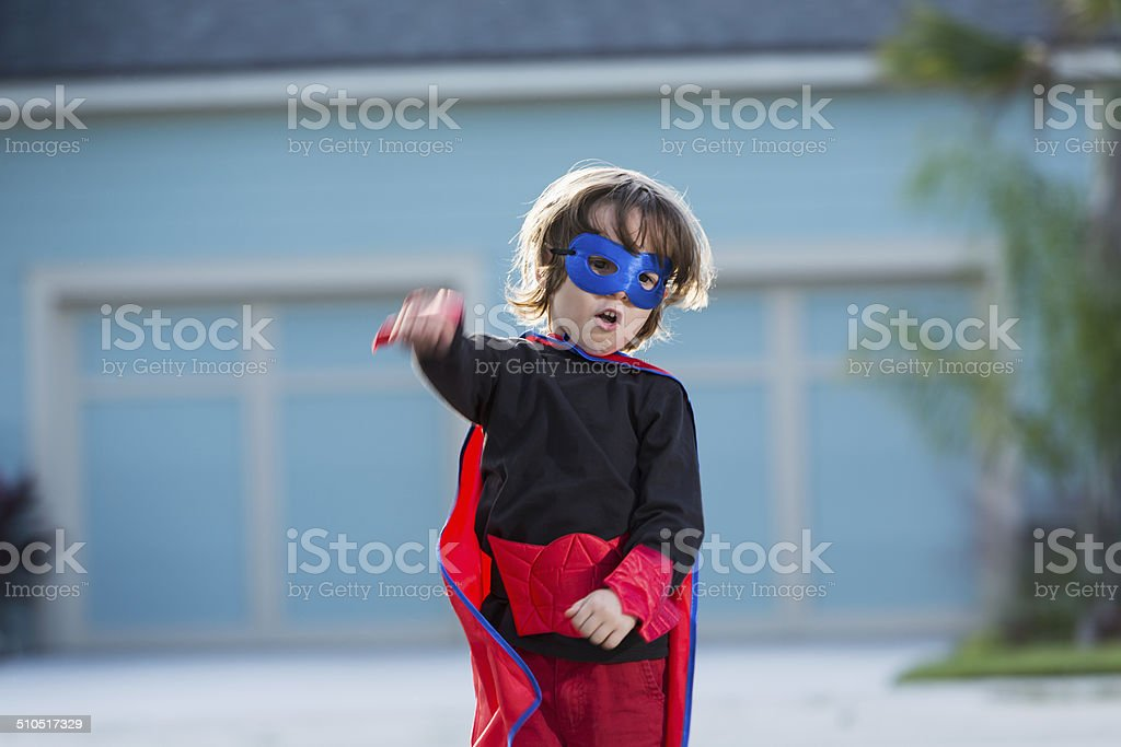 Playful little boy dressed as superhero for Halloween stock photo