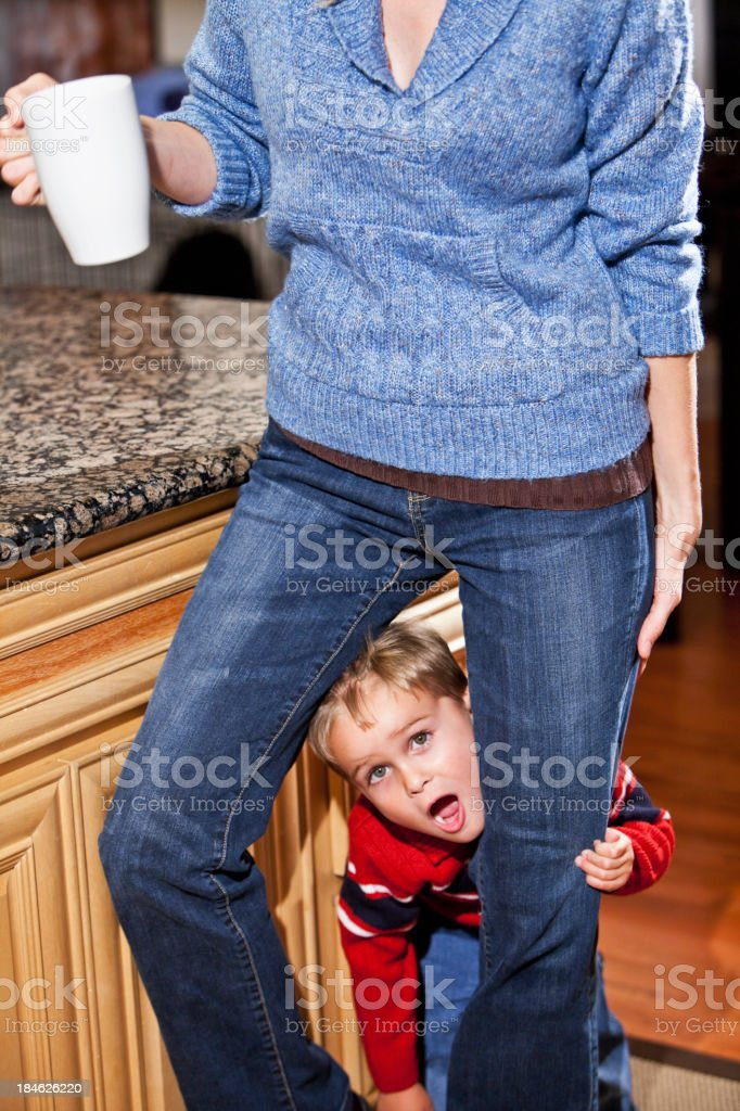 Playful little boy hiding behind mother's leg stock photo