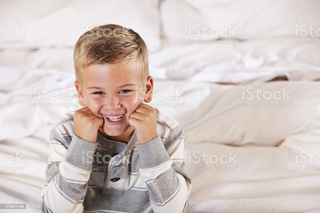 Playful little boy sitting on bed stock photo