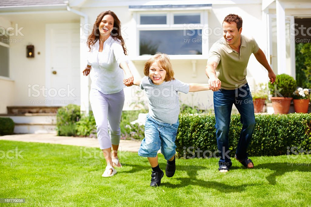 Playful little boy with his parents having fun on grass royalty-free stock photo