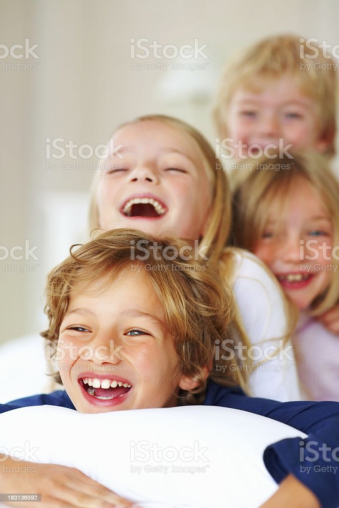 Playful little brothers and sisters enjoying together in bed royalty-free stock photo