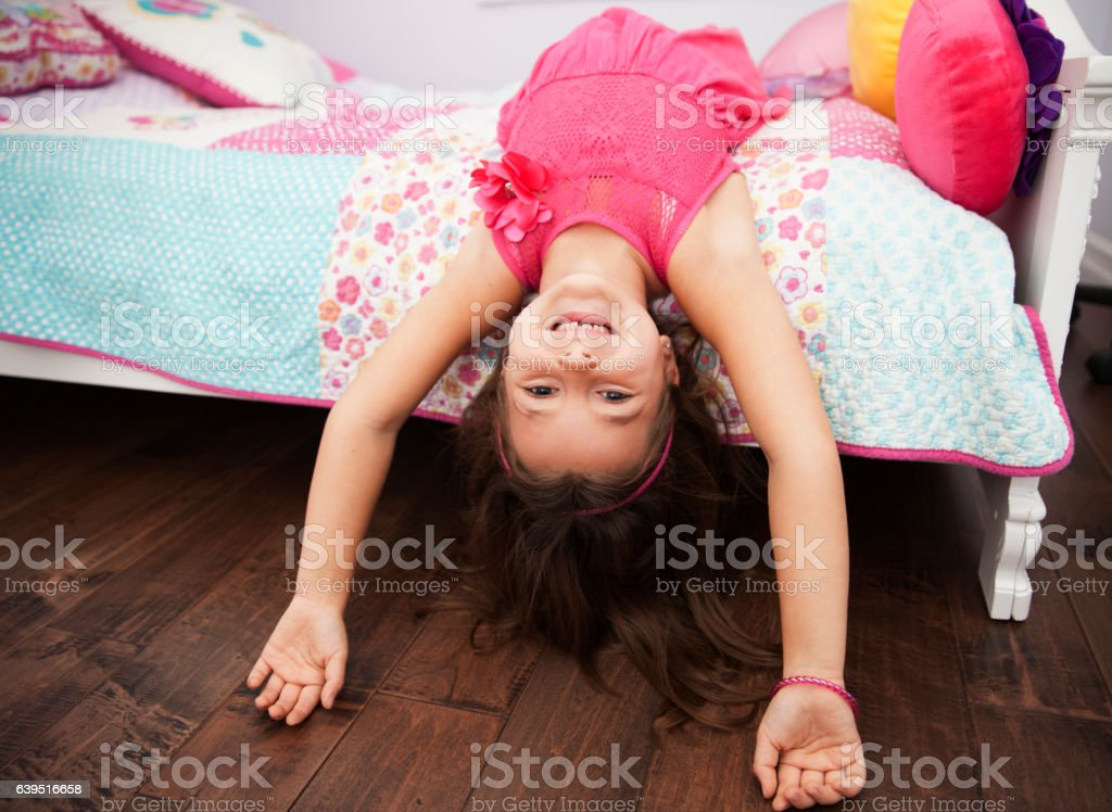 Playful little girl goofing around in her bedroom stock photo