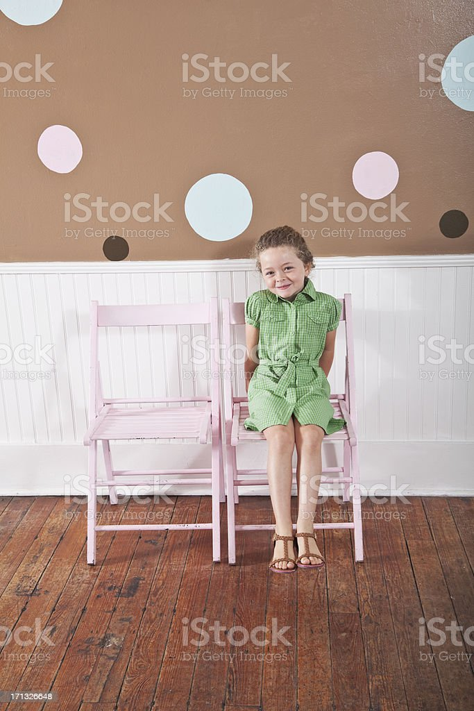 Playful little girl sitting on chair stock photo