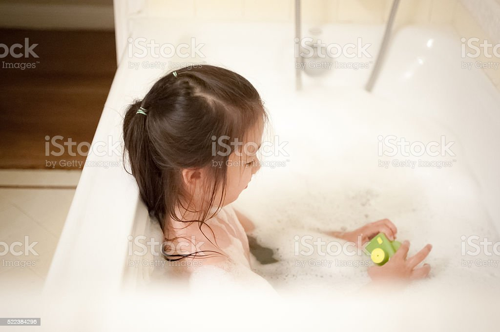 Playful little girl taking bubble bath with a bath toy stock photo