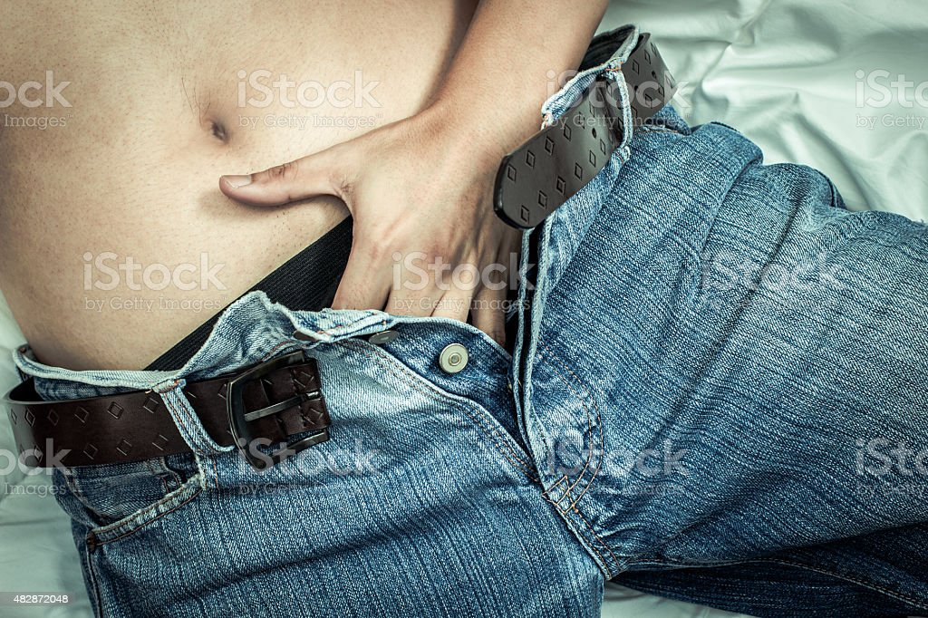 Playful male left hand touching his panties under blue jeans stock photo