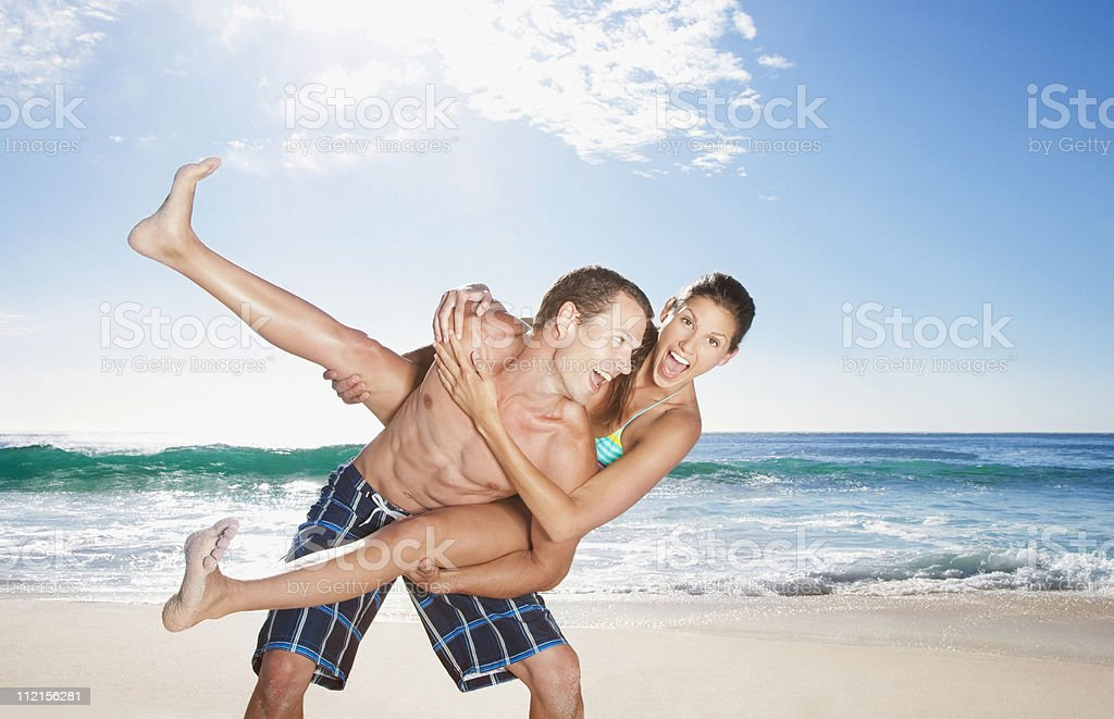 Playful man giving girlfriend piggyback on beach royalty-free stock photo