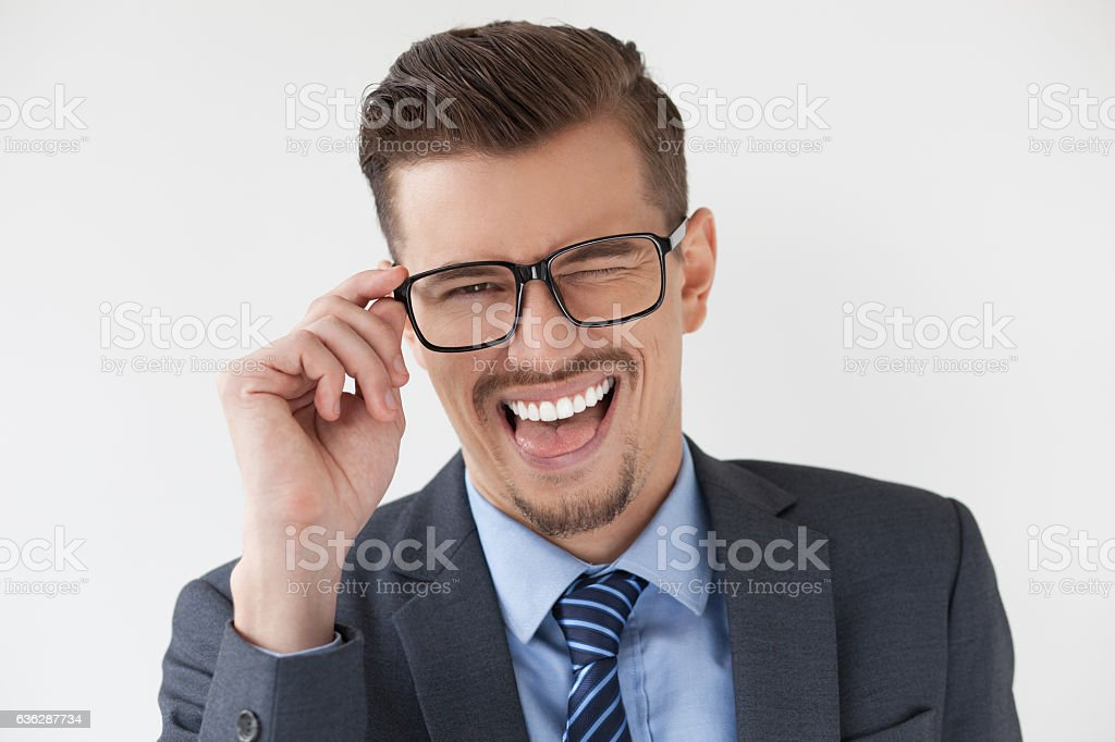 Playful man in eyeglasses sticking tongue out stock photo