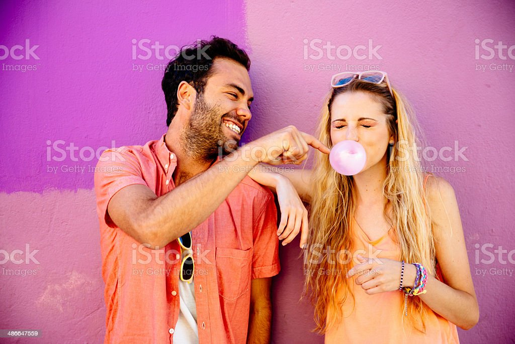 Playful man popping chewing gum bubble girl stock photo