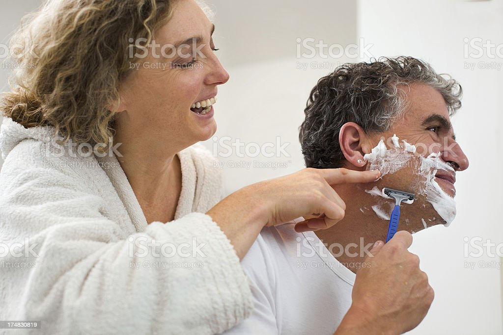 Playful mature couple in bathroom royalty-free stock photo