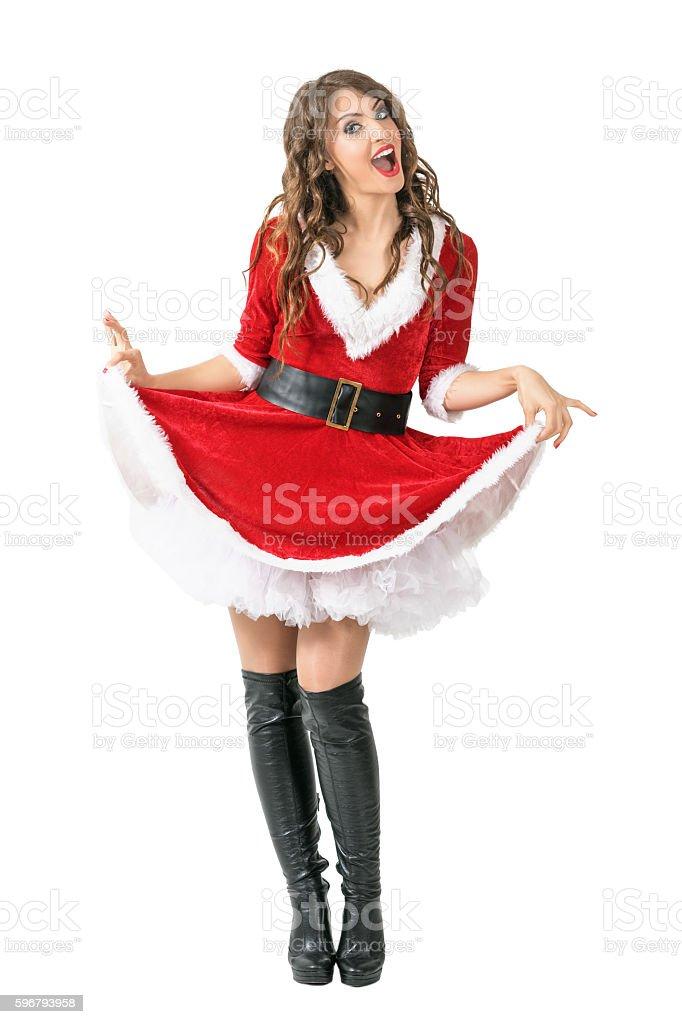 Playful merry Santa woman lifting dress looking at camera. stock photo