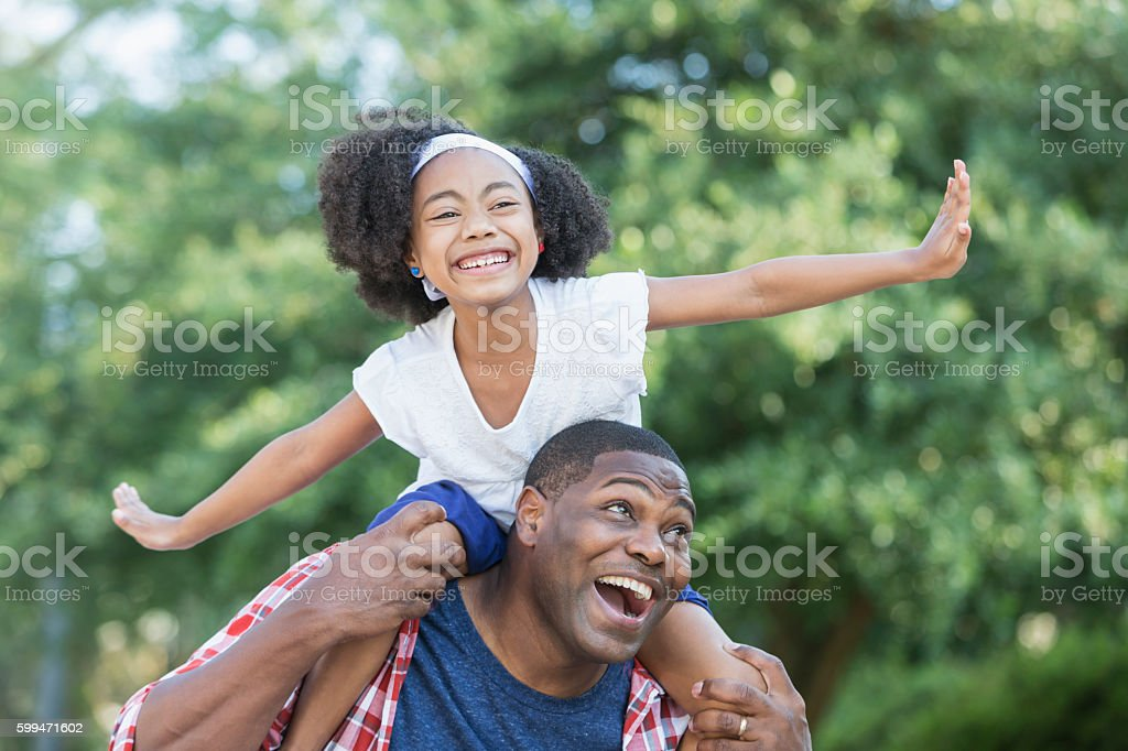 Playful mixed race girl sitting on father's shoulders stock photo