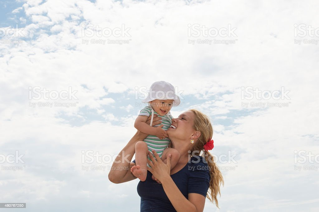 Playful mother and baby on the beach stock photo