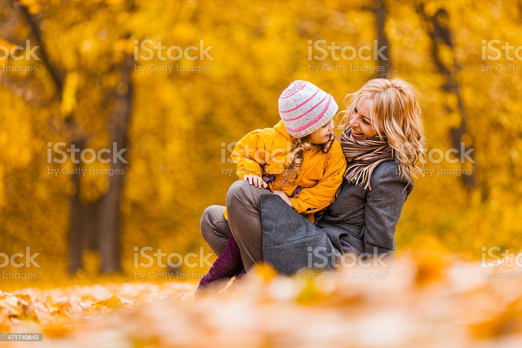 Playful mother and daughter enjoying in autumn park. stock photo