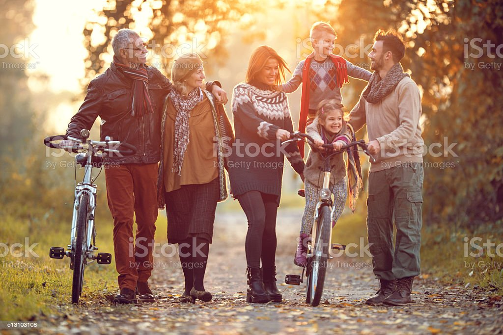 Playful multi-generation family having fun with bikes in nature. stock photo