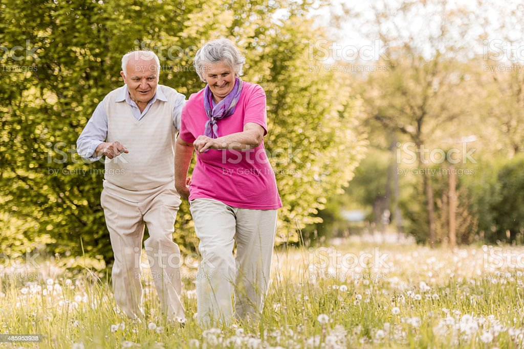 Playful old man chasing his wife in the park. stock photo