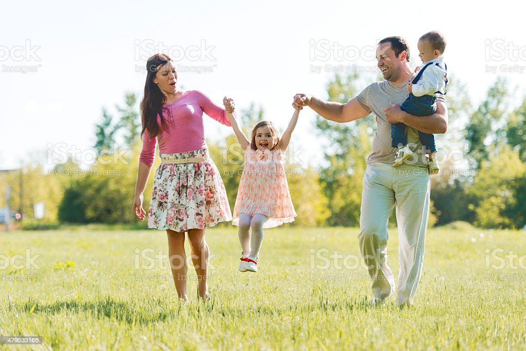 Playful parents having fun with their little children in nature. stock photo